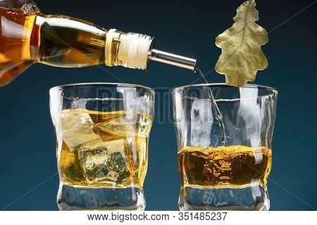 Whiskey Is Pouring From A Bottle Into A Glass. A Glass Of Whiskey With Ice.