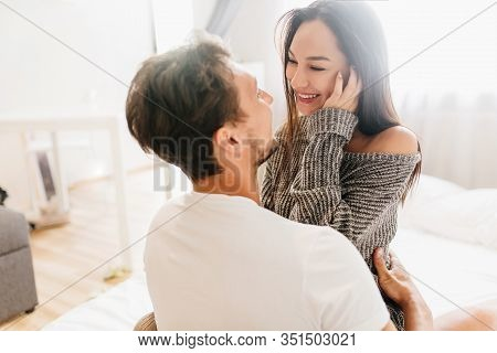 Short-haired Happy Man Embracing Laughing Young Woman In Gray Soft Clothes. Indoor Portrait Of Roman