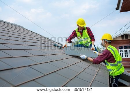 Two Construction Workers Helped To Fixing Roof Tiles, Turning The Gray In The House With The Blue Sk