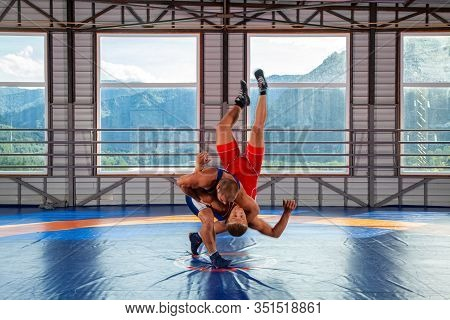 The Concept Of Fair Wrestling. Two Greco-roman  Wrestlers In Red And Blue Uniform Making A Suplex Wr