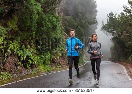 Rain run fit people training jogging in rain weather wearing cold clothing running outdoors in nature autumn season. Active couple on wet park trail jogging. Asian woman, Caucasian man athletes.