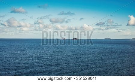 A Creative Imaginative Cerulean Sky With A White Fluffy Clouds Over Water With An Industrial Contain