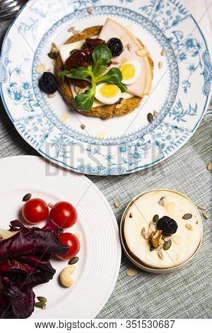 A Rusk With Cheese, Turkey Breast, Quail Egg, Sun-dried Tomato And Valerianella Locusta. Mixed Truff