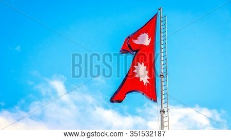 National Flag Of Nepal Attached To The Flagstaff Against Clear Blue Sky.