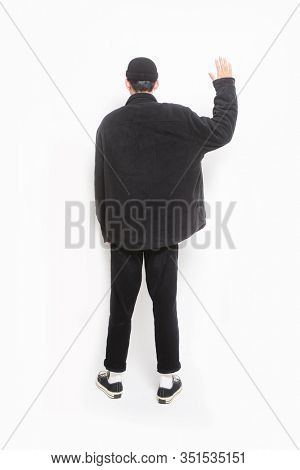 Back view handsome young man walking with a hand in his pocket wearing black clothes, pants standing doing stop sing with palm of the hand isolated on white background; full body, full length
