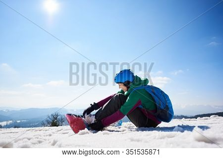 Female Snowboarder Wearing Colorful Clothing And Helmet With Backpack Sitting In Snow, Adjusting Sno