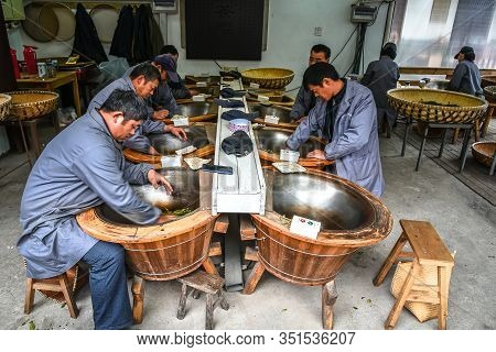 Hangzhou, China - April 6, 2018: In Spring The Men Are Traditional Tea Making Drying Green Tea In Pa
