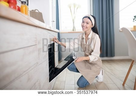 Young Girl In Pinafore Crouching Near The Oven In Kitchen.