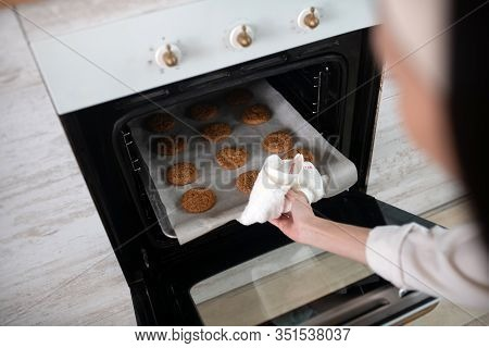 Female Hand Taking Out Baking Sheet From The Oven.