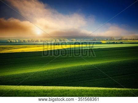 Dramatic view on of sunlit wavy fields of agricultural area at springtime. Location place of Ukraine, Europe. Scenic image of agrarian industry. Photo of ecology concept. Beauty of earth.