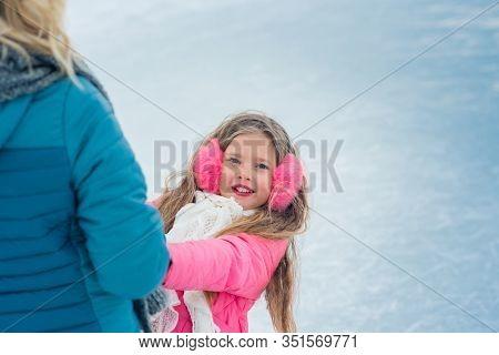 Cheerful Winter Ice Skating Girl Having Fun On Ice Skate Rink Outdoors. The Girl On Ice Skating In P