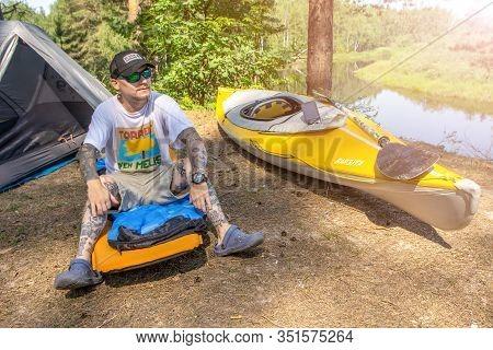 Ryazan, Russia - 06.09.2019: Man With Tatoo Sitting On Camping Mat Near Tent And Kayak