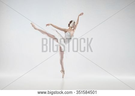 Moving. Young Graceful Classic Ballerina Dancing On White Studio Background. Woman In Tender Clothes