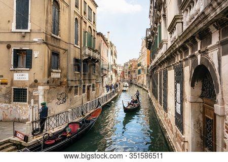 Venice, Italy - May 9, 2019: Venetian Gondolier Punts Gondola Through Narrow Canal Waters Of Venice