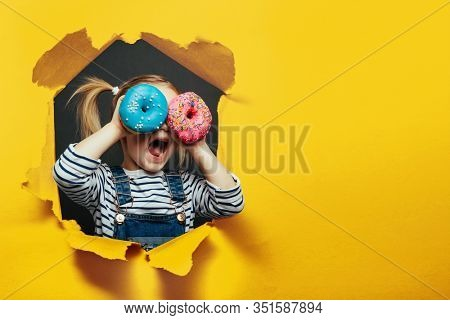 Happy cute girl is having fun played with donuts on yellow background wall. Bright photo of a child.