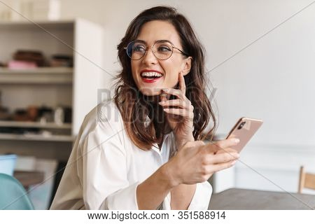 Smiling young beautiful woman using mobile phone while sitting at the cafe table indoors