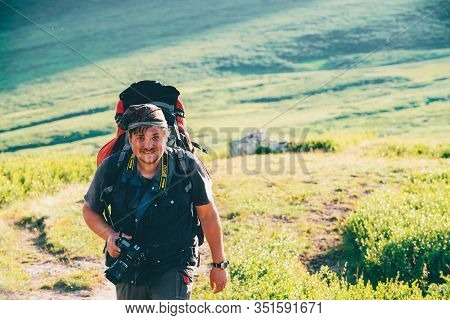 Man With Big Rucksack And Photo Camera Walks On Mountain Trail On Sunny Day. Naturalist Photographer