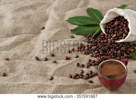Red Cup Coffee (espresso) And Coffee Beans In Burlap Sack On A Burlap Background. Close Up, Soft Foc