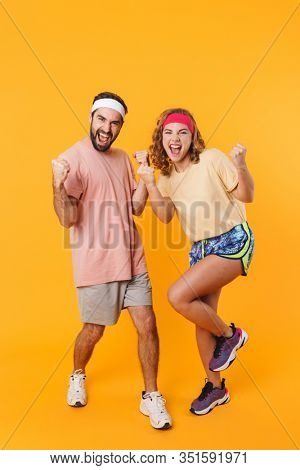 Full length image of athletic happy couple wearing headbands rejoicing and clenching fists in triumph isolated over yellow background