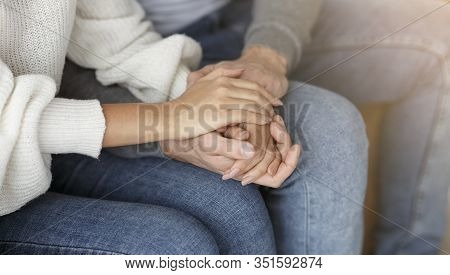 Happy Reconciliation. Unrecognizable Couple Holding Hands Sitting On Couch During Family Therapy Ses