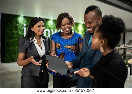 Smiling Group Of A Young African Businesspeople Talking And Using A Digital Tablet Together While St