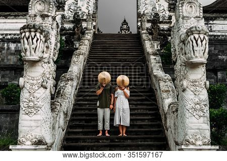 A Couple Stands On The Stairs Of The Baltic Temple And Cover Their Faces With Rice Caps. Man And Wom