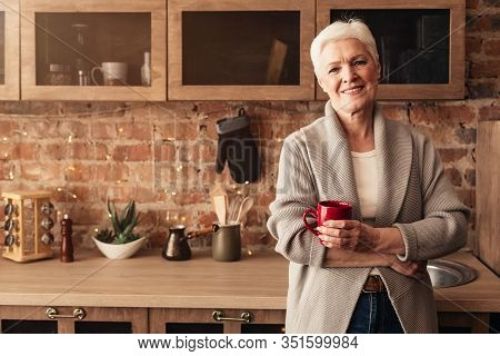 Portrait Of Happy Elderly Woman Standing In Kitchen With Cup Of Coffee In Hands And Looking At Camer