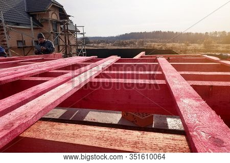 Installation Of Wooden Beams In The Construction Of The Roof System Of The Rafters, The Worker Hamme