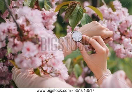 Stylish Watch On Woman Hand On Flower Background. Woman Looking At Her Watch.