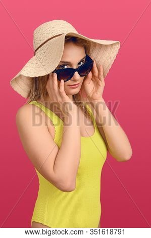 Attractive Chic Young Woman In Summer Outfit With A Large Floppy Sunhat Peering Over The Top Of Her