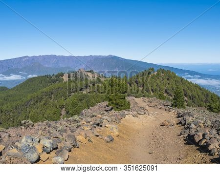 Volcanic Landscape With Lush Green Pine Trees, Colorful Volcanoes And Lava Rock Field Along Path Rut