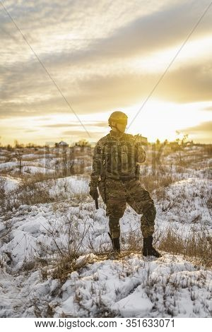 Equipped Army Soldier Man In The Winter Khaki Camouflage Is Patrolling Or Patrol Field Territory. Co