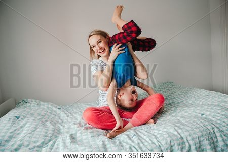 Smiling Caucasian Mother And Boy Son Playing Together In Bedroom At Home. Mom Holding Child Upside D