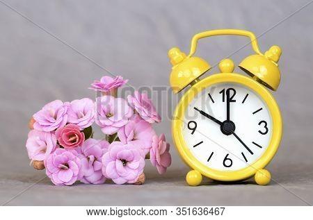 Yellow Alarm Clock And Flowers On Grey Background, Spring Forward, Springtime, Daylight Savings Time