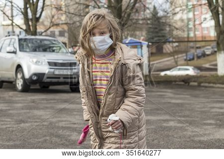 Girl With White Hair On Her Face A Medical Mask. In The Hands Of A Children's Toy. Shallow Depth Of