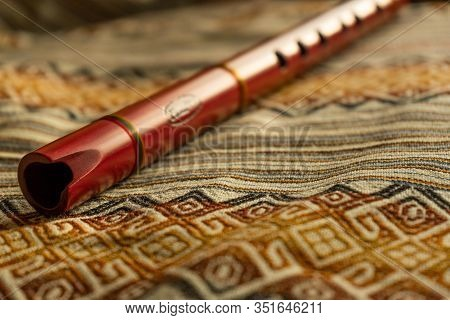 Close Up View Of A Quena (peruvian Flute) On Colorful Peruvian Textiles. Natural Light. Traditional