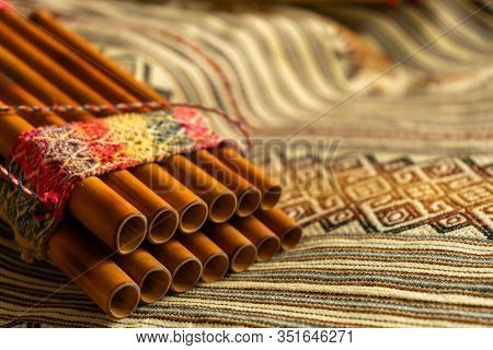 Close Up View Of Peruvian Pan Flute, On A Coloured Poncho. Natural Light. Concept Of Traditional And