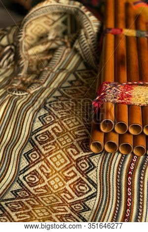 Peruvian Pan Flute, On A Coloured Poncho. Natural Light. Concept Of Traditional Andean Music.