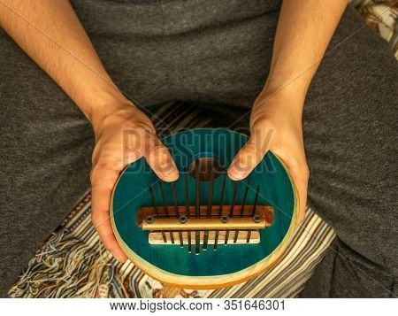 Caucasian Young Man Playing The Kalimba. Traditional African Instrument. Natural Light. Traditional