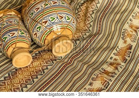 Moroccan Ceramic And Leather Drums, Lying On Coloured Textiles. Natural Light. Traditional Music Con