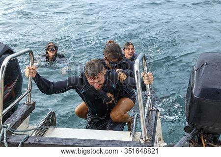 Divers Help Other Divers Get On Boat After Diving, Sri Lanka,
