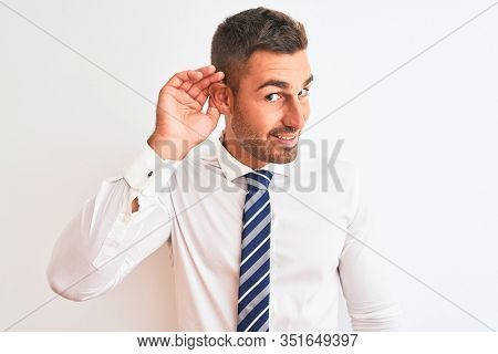 Young handsome elegant business man over isolated background smiling with hand over ear listening an hearing to rumor or gossip. Deafness concept.