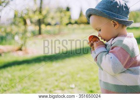 Little Child Holding In Hand Easter Egg In Spring Park. Kids Hunt For Eggs Outdoors. Festive Family