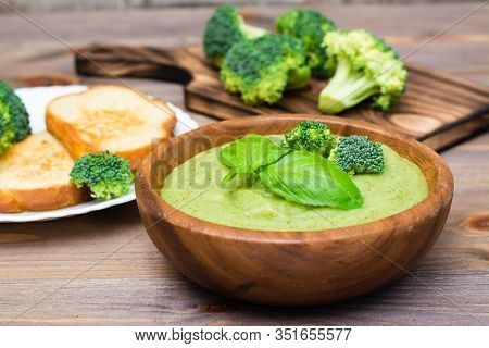 Ready To Eat Fresh Hot Broccoli Puree Soup With Pieces Of Broccoli And Basil Leaves In A Wooden Plat