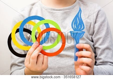 Olympics, Japan, Tokyo, Summer, 2020. A Child's Hand Holds Multi-colored Rings And A Blue Torch Made