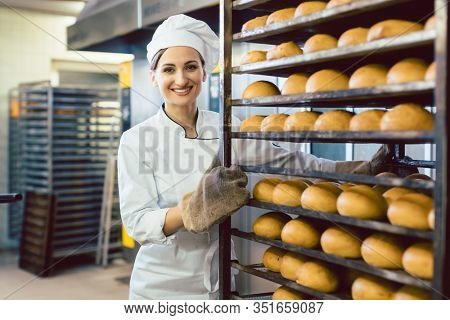 Baker woman rolling trays with fresh bread thru the bakery