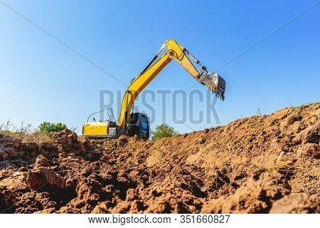 Backhoe Digging Up Soil To Prepare Agricultural Land.
