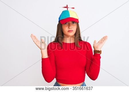 Young beautiful girl wearing fanny cap with propeller standing over isolated white background clueless and confused expression with arms and hands raised. Doubt concept.