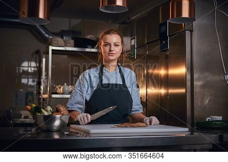 Confident And Serious Woman Chef Standing In A Dark Kitchen Next To A Big Bowl Of Fresh Vegetables A