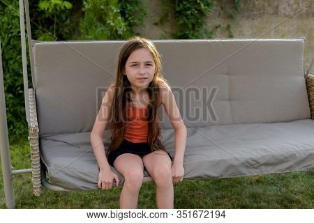 Beautiful Young Woman Swinging Outdoor. Girl On A Garden Swing. Girl 8 Or 9 Years Old On A Swing. Th